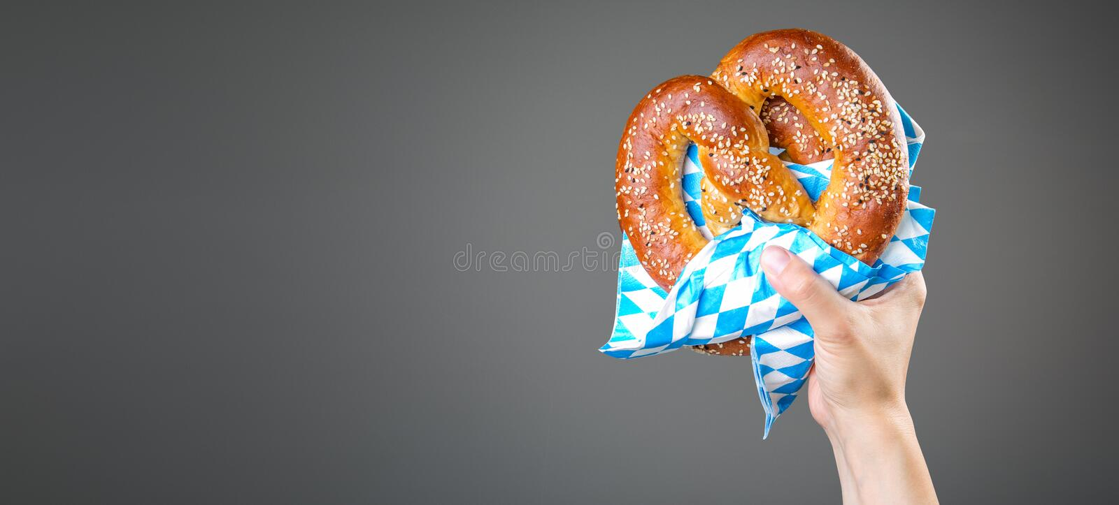Oktoberfest concept - hands holding beer and pretzel royalty free stock photos
