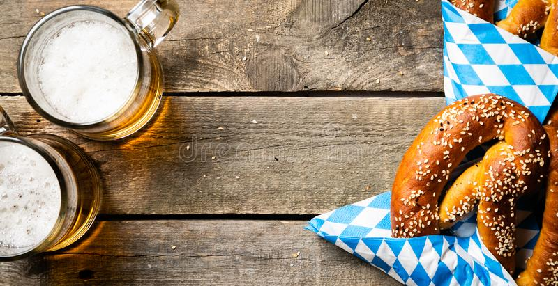 Oktoberfest concept - pretzels and beer on rustic wood background royalty free stock images