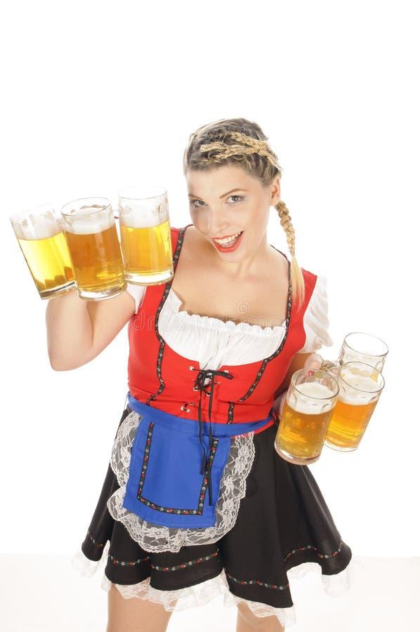 Oktoberfest, empregada de mesa nova no dirndl com muitas canecas de cerveja fotografia de stock