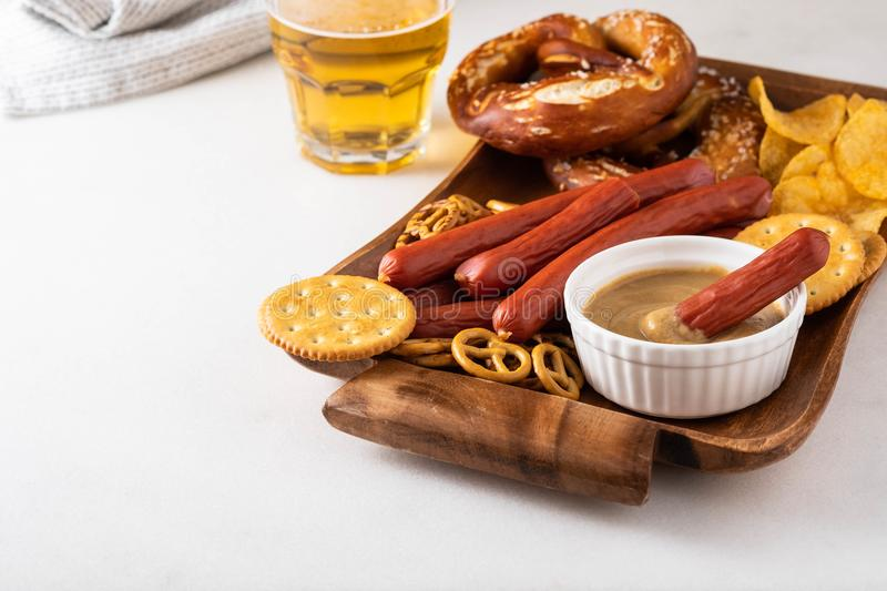 Oktoberfest food, appetizing beer snacks set for big company. Grilled sausages, salami, chips, pretzel crackers and. French fries served with spicy tomato sauce royalty free stock images
