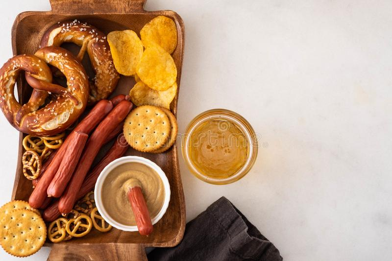 Oktoberfest food, appetizing beer snacks set for big company. Grilled sausages, salami, chips, pretzel crackers and. French fries served with spicy tomato sauce stock photo