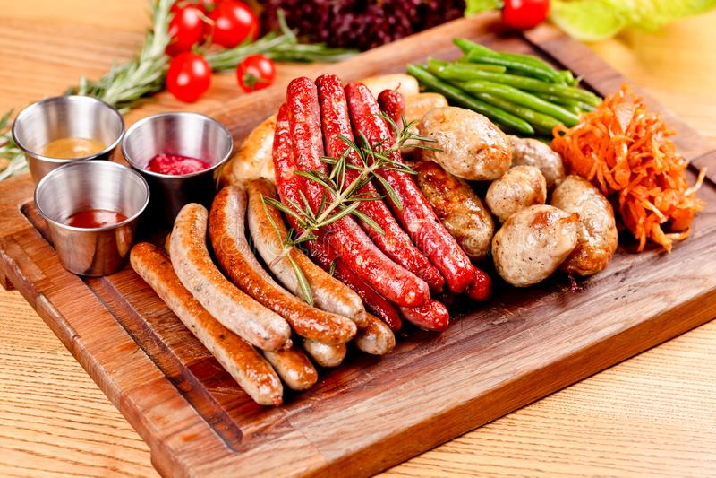 Oktoberfest food menu. Assorted grilled sausages, sauerkraut, green beans on wooden cutting board. Close up stock photo