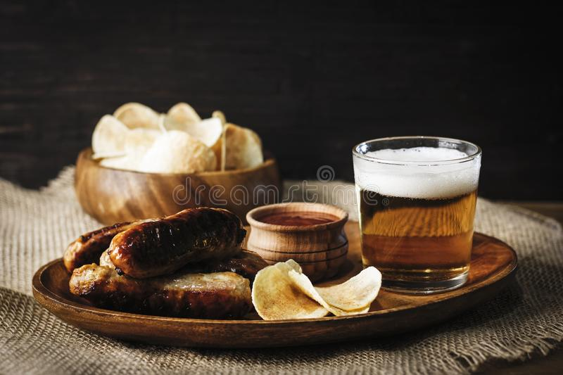 Oktoberfest food menu, beer in a glass on a wooden tray next to traditional snacks: bavarian sausages, chips and red sauce, on a royalty free stock image