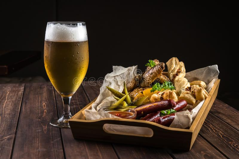 Oktoberfest food snacks concept with copy space. Wooden table with a glass of cold beer with water droplets and a big wooden box stock image