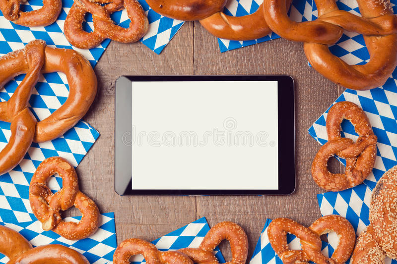 Oktoberfest german beer festival background with digital tablet and pretzel. View from above royalty free stock image