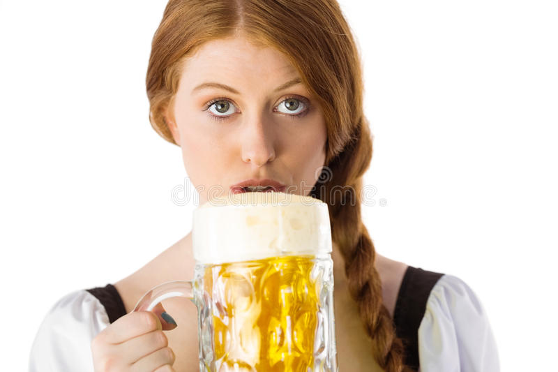 Oktoberfest girl drinking jug of beer. On white background royalty free stock images
