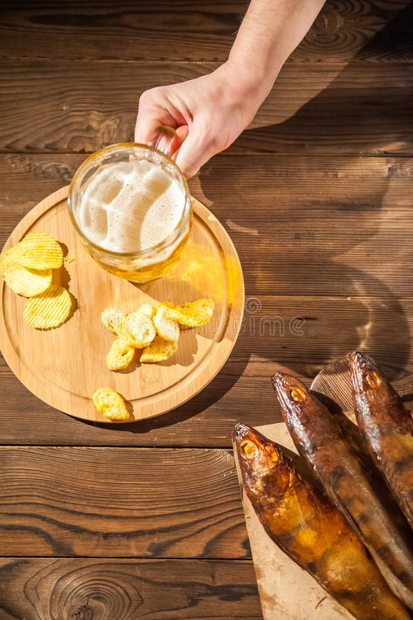 Oktoberfest holiday concept. Beer, smoked fish, chips on a wooden textural background in a dark key. Beer in a glass, fish in pape. R close-up and copy space stock image