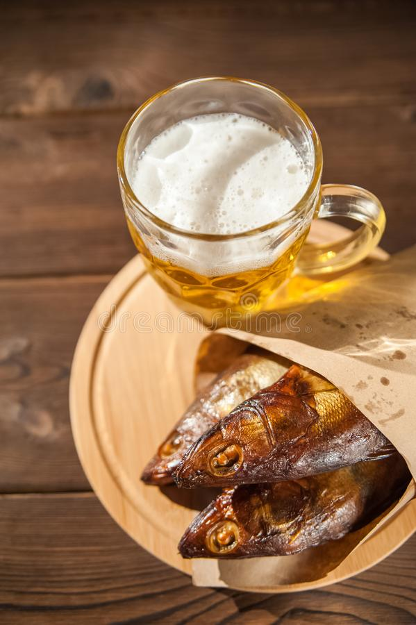 Oktoberfest holiday concept. Beer, smoked fish, chips on a wooden textural background in a dark key. Beer in a glass, fish in pape. R close-up and copy space royalty free stock photo