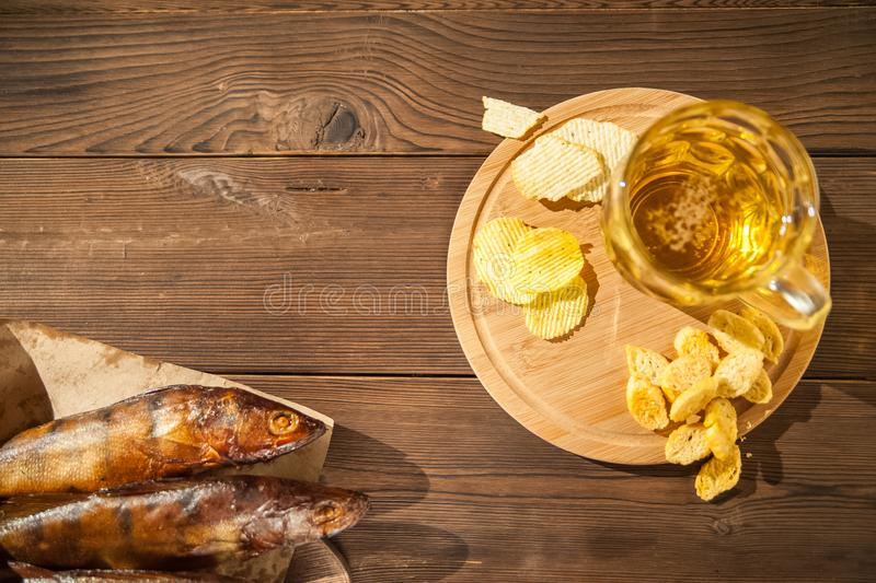 Oktoberfest holiday concept. Beer, smoked fish, chips on a wooden textural background in a dark key. Beer in a glass, fish in pape. R close-up and copy space stock photography