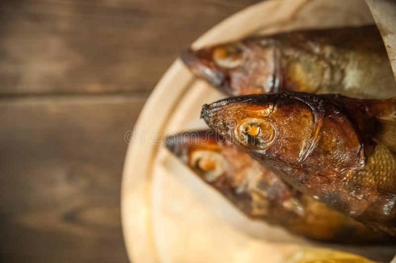 Oktoberfest holiday concept. Beer, smoked fish, chips on a wooden textural background in a dark key. Beer in a glass, fish in pape. R close-up and copy space royalty free stock photos