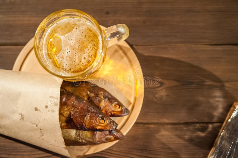 Oktoberfest holiday concept. Beer, smoked fish, chips on a wooden textural background in a dark key. Beer in a glass, fish in pape. R close-up and copy space stock photos
