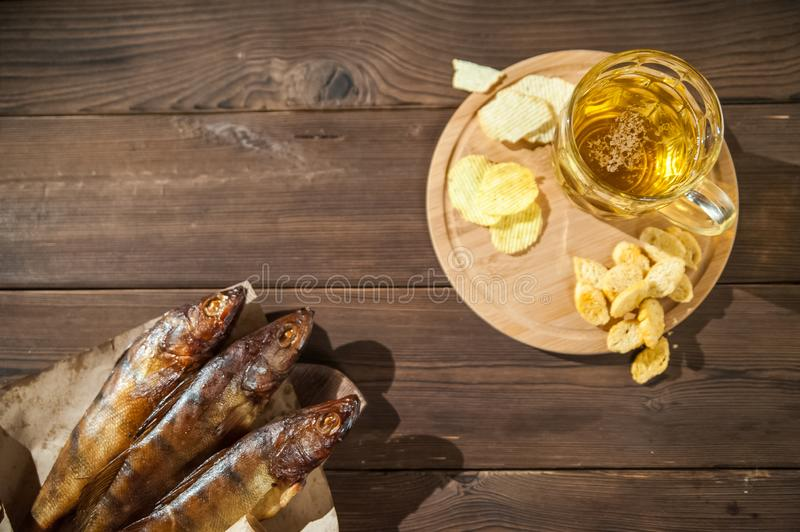Oktoberfest holiday concept. Beer, smoked fish, chips on a wooden textural background in a dark key. Beer in a glass, fish in pape. R close-up and copy space stock photo
