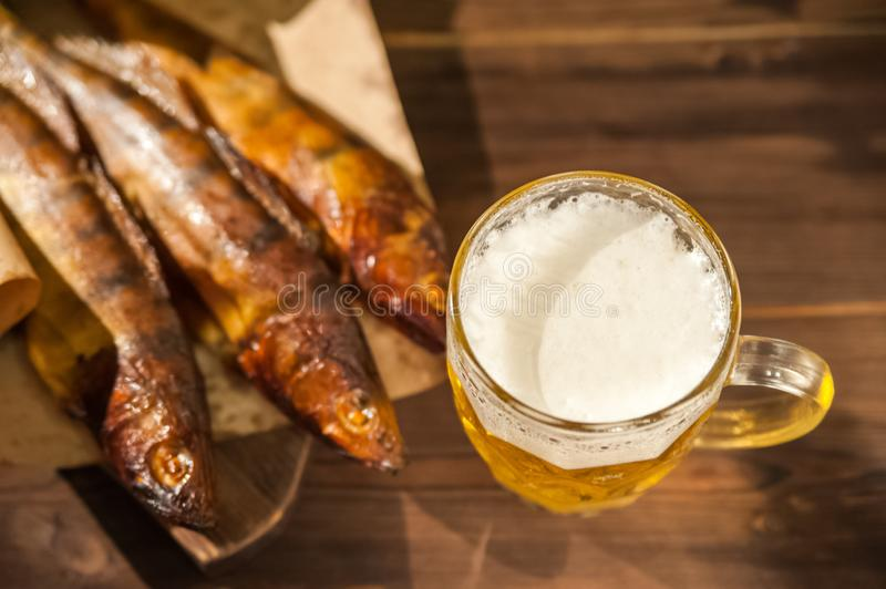 Oktoberfest holiday concept. Beer, smoked fish, chips on a wooden textural background in a dark key. Beer in a glass, fish in pape. R close-up and copy space royalty free stock image