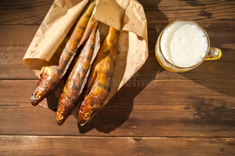 Oktoberfest holiday concept. Beer, smoked fish, chips on a wooden textural background in a dark key. Beer in a glass, fish in pape. R close-up and copy space royalty free stock photography