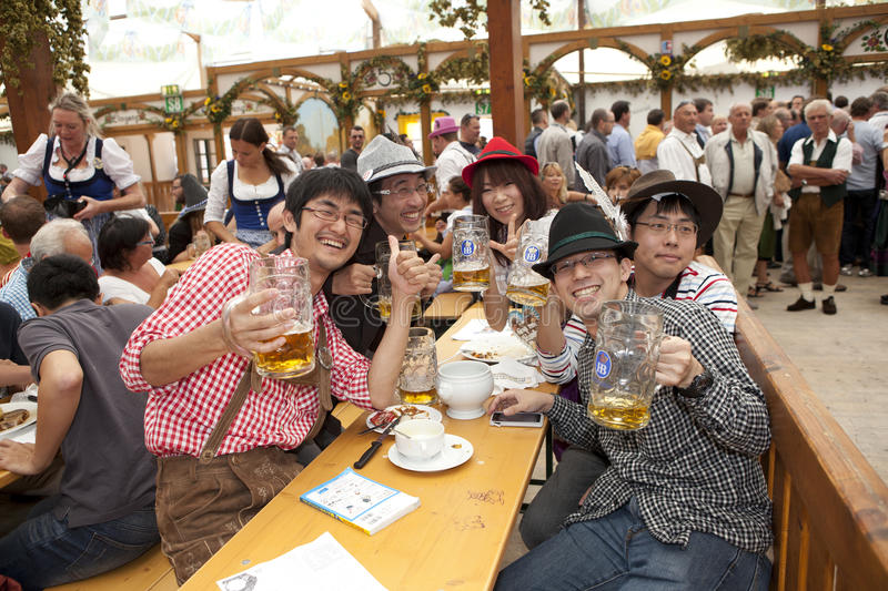 Oktoberfest Japanese visitors. Japanese visitors to sit in the tent at the Oktoberfest and drink beer in a beer mug royalty free stock photography