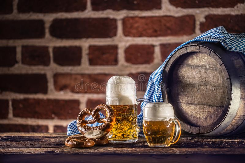 Oktoberfest large and small beer with pretzel wooden barrel and blue tablecloth.  stock images