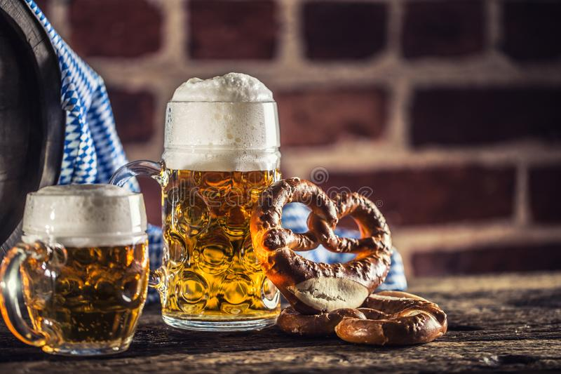 Oktoberfest large and small beer with pretzel wooden barrel and blue tablecloth.  royalty free stock photo