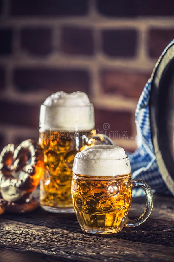 Oktoberfest large and small beer with pretzel wooden barrel and blue tablecloth.  stock photos
