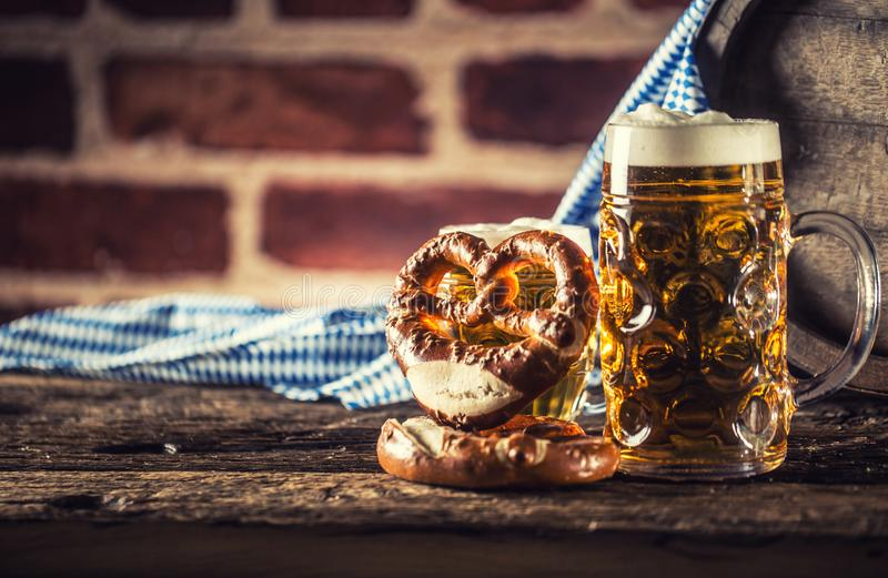 Oktoberfest large and small beer with pretzel wooden barrel and blue tablecloth.  stock image
