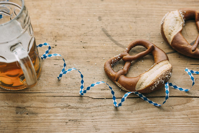 Oktoberfest: Masskrug of beer, Pretzels and bavarian streamer. On rustic wooden table royalty free stock images
