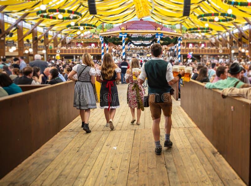 Oktoberfest, Munich, Alemanha Garçom que guarda cervejas, fundo interior da barraca fotos de stock royalty free