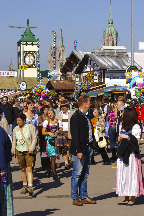 Oktoberfest in Munich. MUNICH, GERMANY - SEPTEMBER 23, 2014: The Oktoberfest in Munich is the biggest beer festival of the world. The visitors are walking at the royalty free stock image
