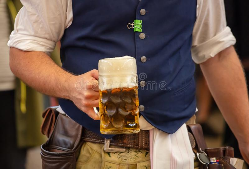Oktoberfest, Munich, Germany. Waiter serving beer, closeup view. Oktoberfest, Munich, Germany. Waiter with traditional costume holding one beer, closeup view royalty free stock photos