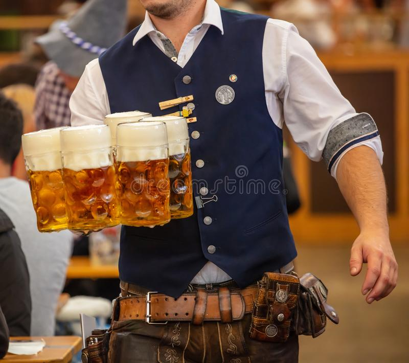 Oktoberfest, Munich, Germany. Waiter serving beers, closeup view. Oktoberfest, Munich, Germany. Waiter with traditional costume serving beers, closeup view royalty free stock images