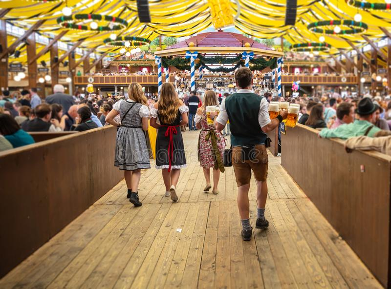 Oktoberfest, Munich, Germany. Waiter holding beers, tent interior background royalty free stock photos