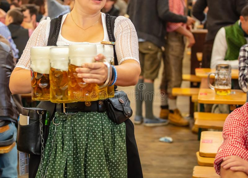 Oktoberfest, Munich, Germany. Waiter with traditional costume holding beers. Oktoberfest, Munich, Germany. Woman waiter with traditional costume holding beers stock photography