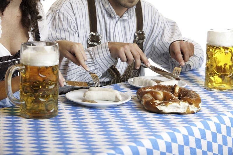 Oktoberfest Paare, die Bierstein und -mahlzeit haben stockfotos