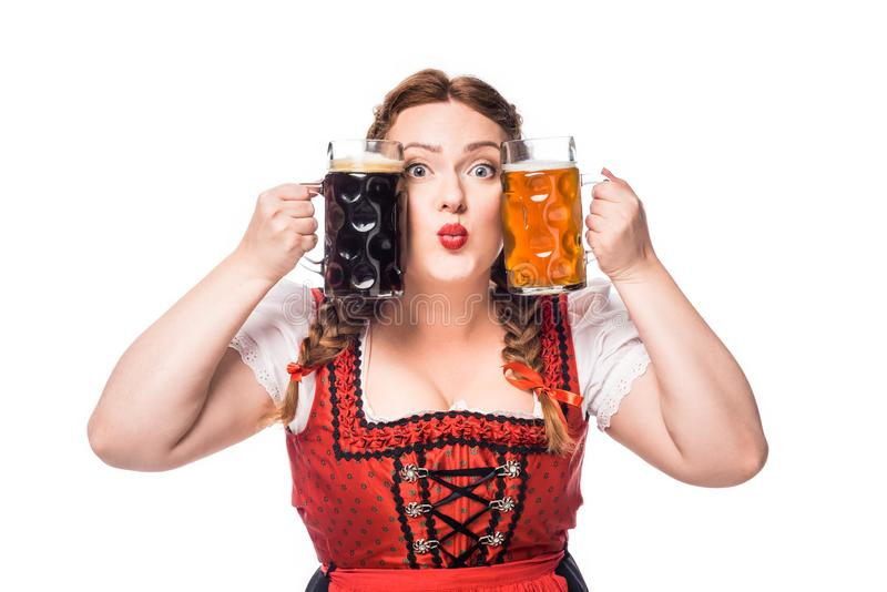 Oktoberfest waitress in traditional bavarian dress holding mugs with light and dark beer. Isolated on white background stock image