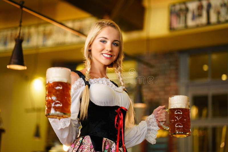 Oktoberfest. Young waitress with beer mugs stock image