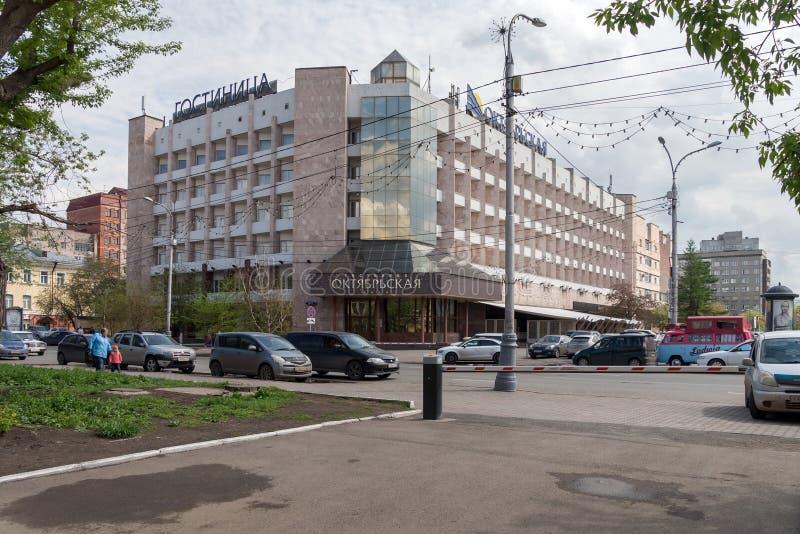 Oktyabrskaya hotell med bilar framme av det på Mira Avenue i det gamla centret av Krasnoyarsk på en molnig vårdag arkivbild