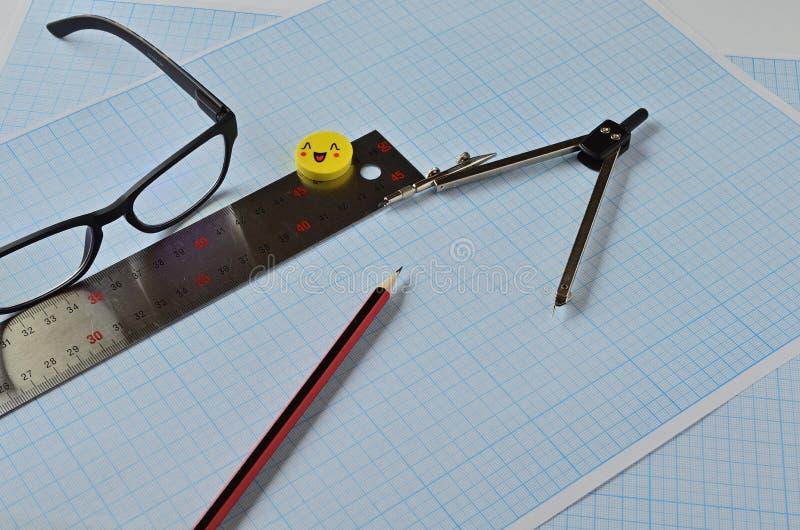 Okulary i obiekty do rysowania na papierze milimetrowym obrazy stock