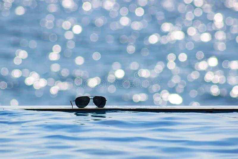 Okulary przeciwsłoneczni blisko krawędzi pływacki basen (śródpolnym) Lata pojęcie z kopii przestrzenią Światła słonecznego bokeh obrazy stock