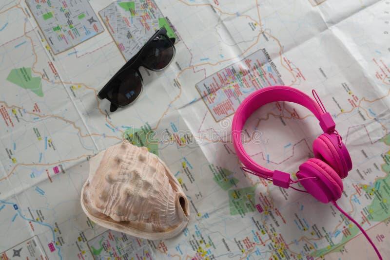 Okulary przeciwsłoneczni, hełmofony i seashell na mapie, zdjęcia stock