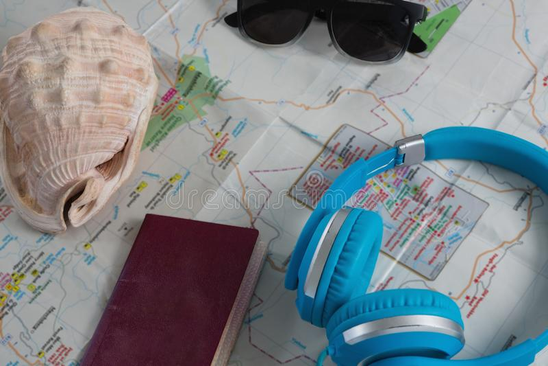 Okulary przeciwsłoneczni, hełmofony, paszport i seashell na mapie, zdjęcia stock