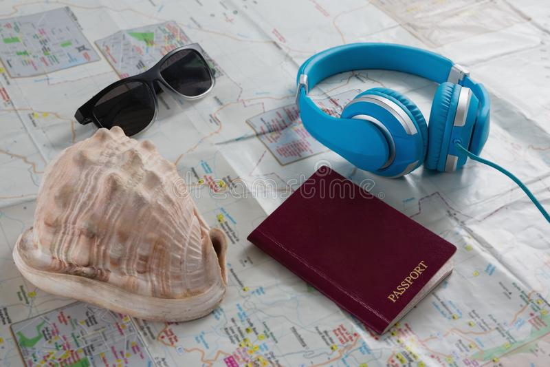 Okulary przeciwsłoneczni, hełmofony, paszport i seashell na mapie, obraz royalty free