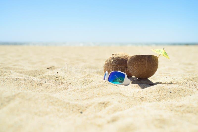 Okulary przeciwsłoneczni i koks z napojem na plaży zdjęcie stock