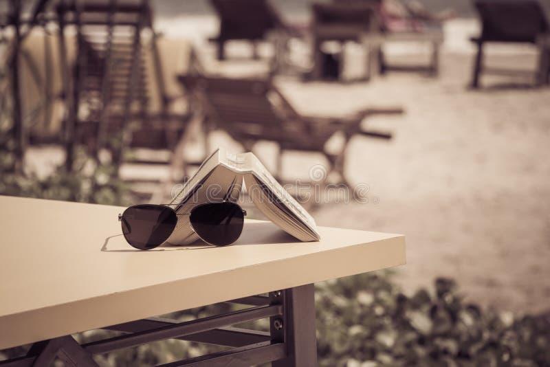 Okulary przeciwsłoneczni i książkowy lying on the beach na stole w tropikalnej plażowej kawiarni zdjęcia royalty free