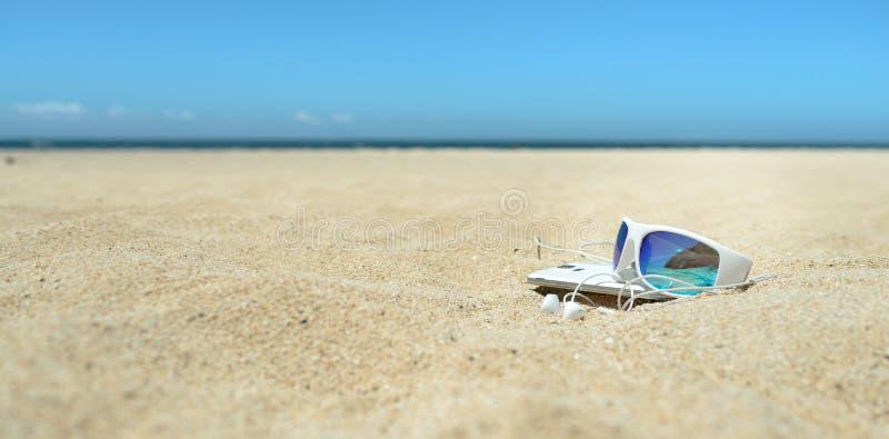 Okulary przeciwsłoneczni i telefon na plaży obraz stock