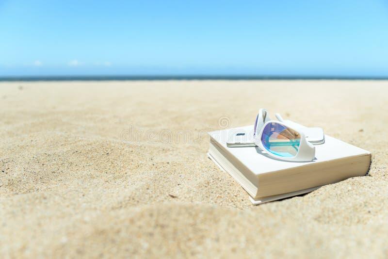 Okulary przeciwsłoneczni, książka i telefon na plaży, zdjęcia royalty free