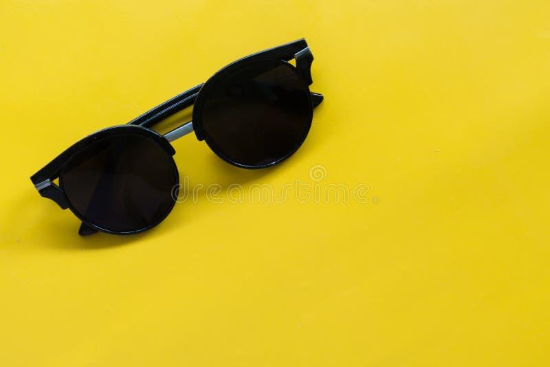 Okulary przeciwsłoneczni na Żółtym tle opróżniają przestrzeń fotografia royalty free