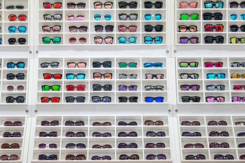 Okulary przeciwsłoneczni na sprzedaż pokazu półce w okularach przeciwsłonecznych robią zakupy przy miastem obrazy royalty free