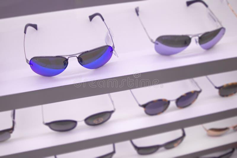 Okulary przeciwsłoneczni robią zakupy z ilość cieniami na odgórnej półce w drogim pr zdjęcia stock