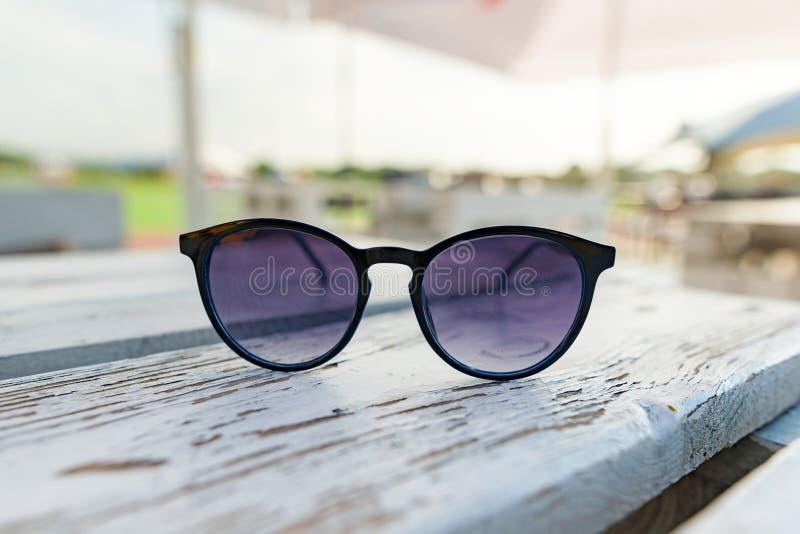 Okulary przeciwsłoneczni symbol lato, tło stołu plenerowa lato kawiarnia biała drewniana powierzchnia zdjęcia stock