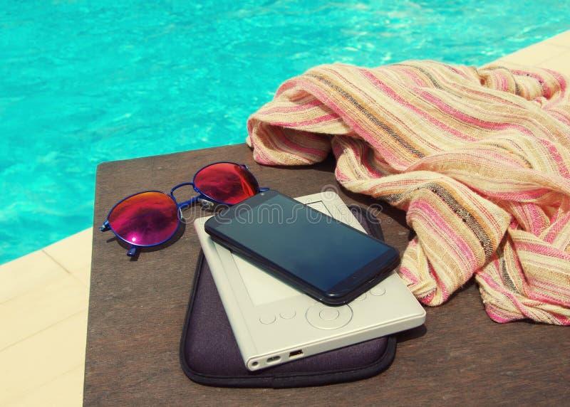 Okulary przeciwsłoneczni, telefon komórkowy, ebook czytelnik i kobieta szalik blisko basenu, fotografia stock