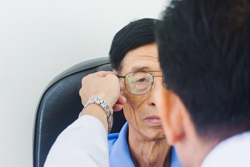 Okulistów męskie ręki stawiający szkła na starszych osobach obsługują badać jego oko obraz royalty free