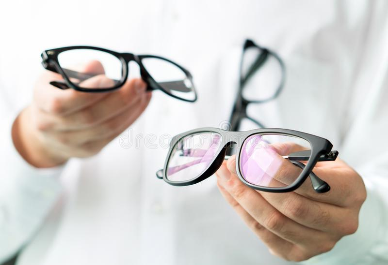 Okulista porównuje obiektywy lub pokazuje klientowi różne opcje obrazy stock